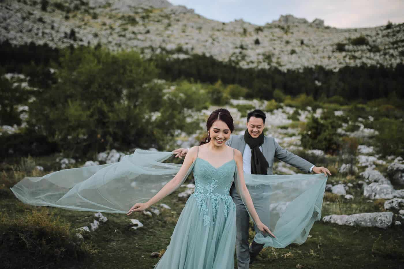 asian couple on their croatia honeymoon during photosession in green gown